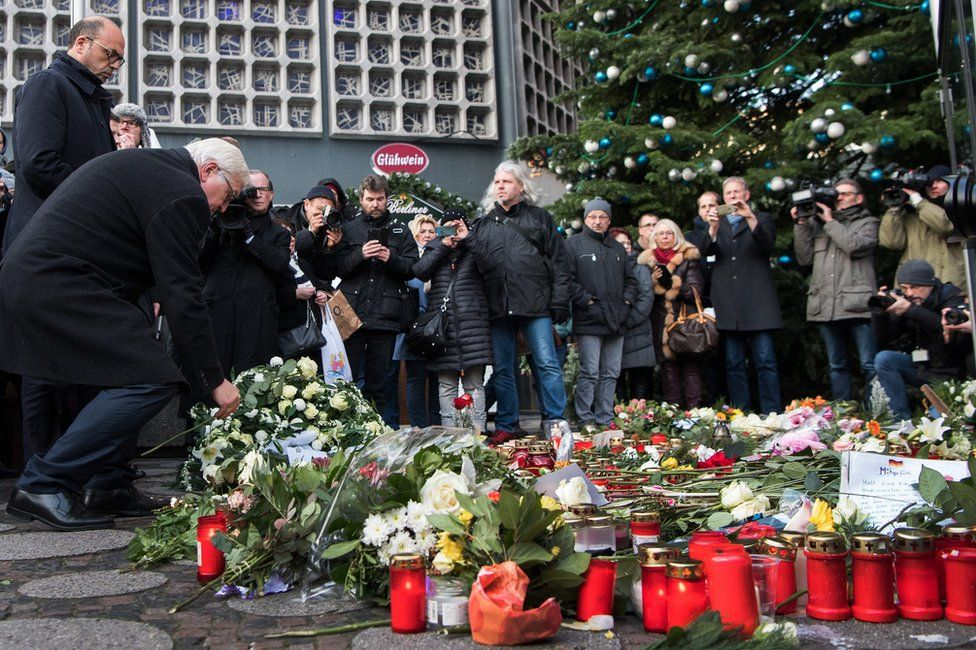 German Foreign Minister Frank-Walter Steinmeier (2-L) and his Italian counterpart Angelino Alfano (L) lay flowers and light candles at the site of the attack at the Christmas market at Breitscheidplatz in Berlin, Germany, 21 December