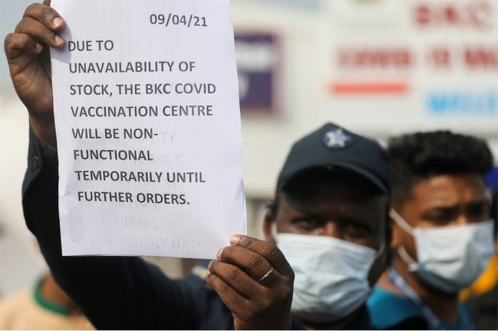 A guard holds up a notice to inform people about the shortage of coronavirus disease (COVID-19) vaccine supplies at a vaccination centre, in Mumbai, India, April 9, 2021.
