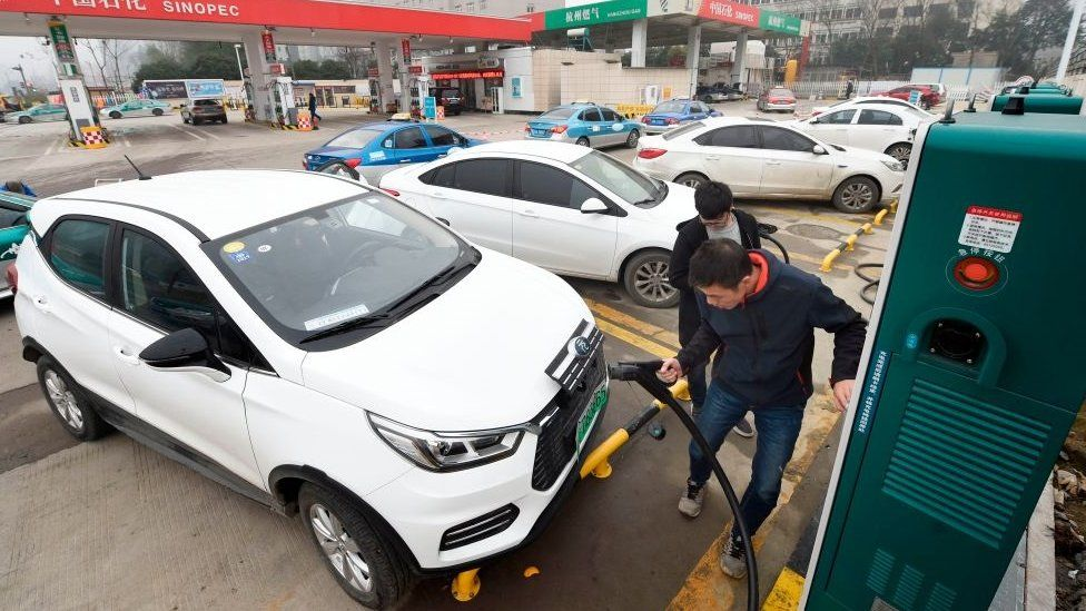 This photo taken on January 14, 2019 shows a man plugging in an electric vehicle at a Sinopec service station in Hangzhou, in China's eastern Zhejiang province.