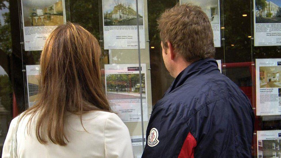 People looking in estate agent's window