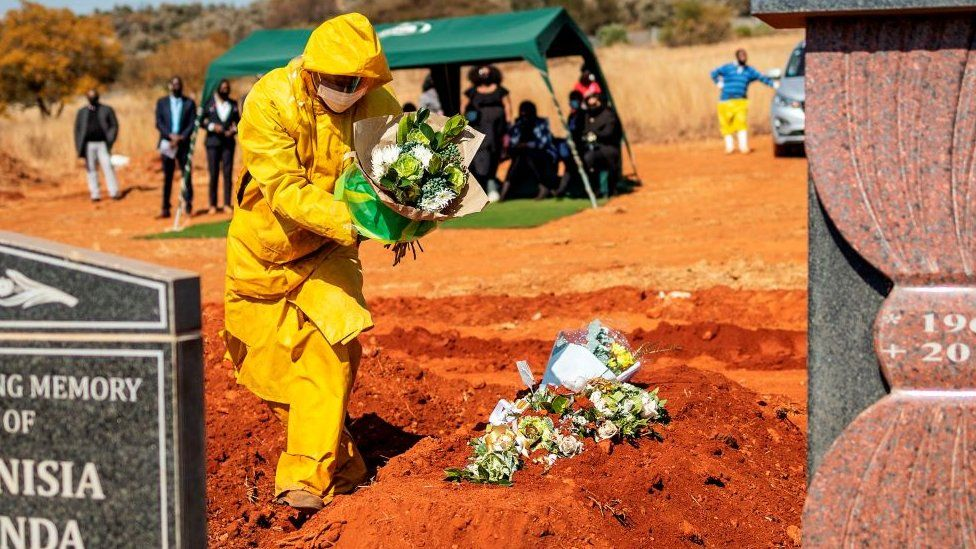 An undertaker wearing personal protective equipment (PPE) lays flowers on the grave containing the remains of Modise Motlhabane, who died of COVID-19 coronavirus, during the funeral at the Westpark cemetery in Johannesburg, on July 22, 2020.