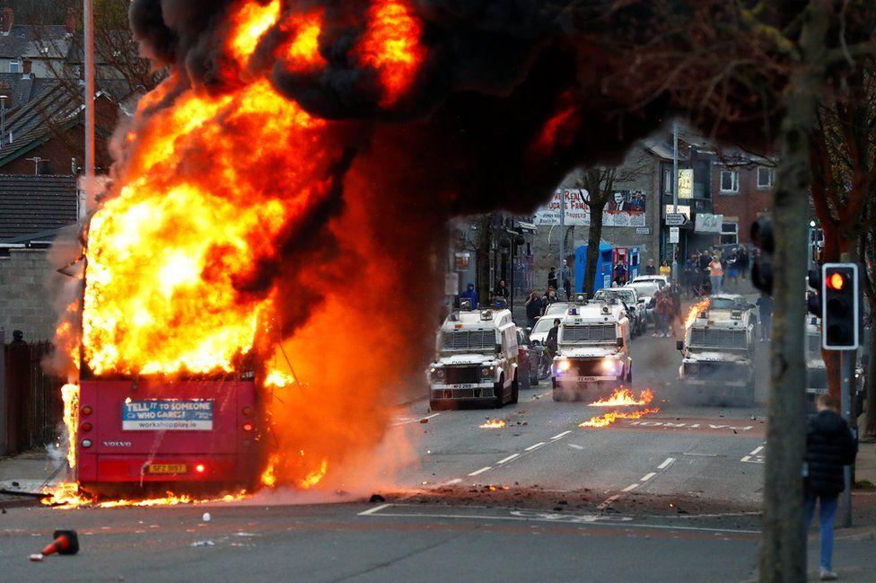 A bus burns on a street in west Belfast