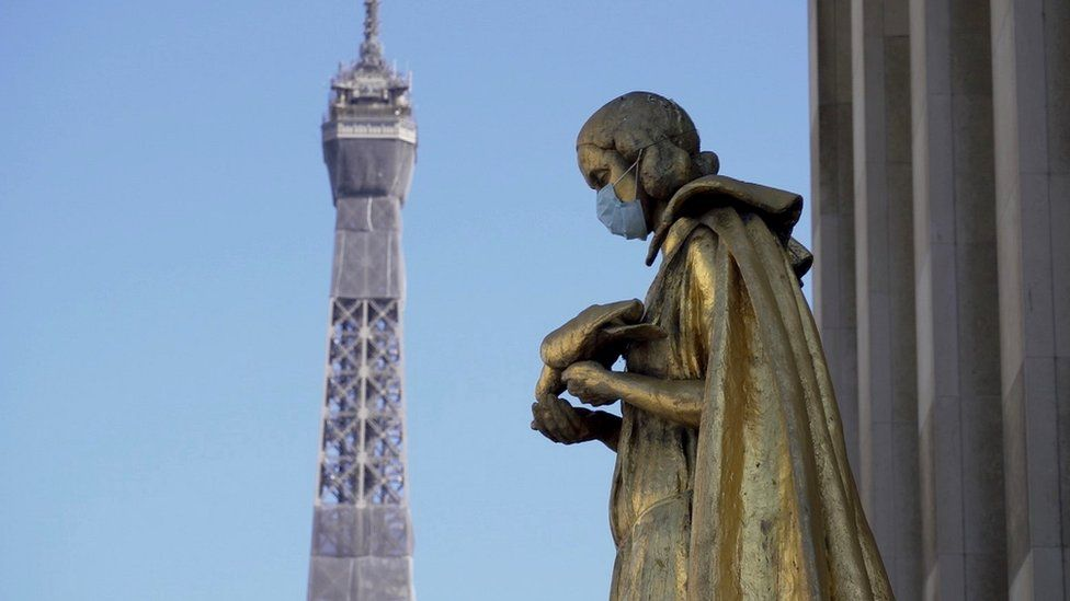 Masked statue with Eiffel Tower in background