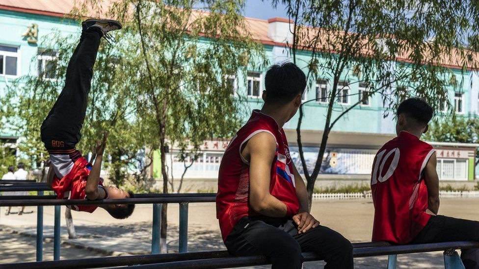 Boys practice on the gymnastic parallel bars in their school playground in Hoeryong