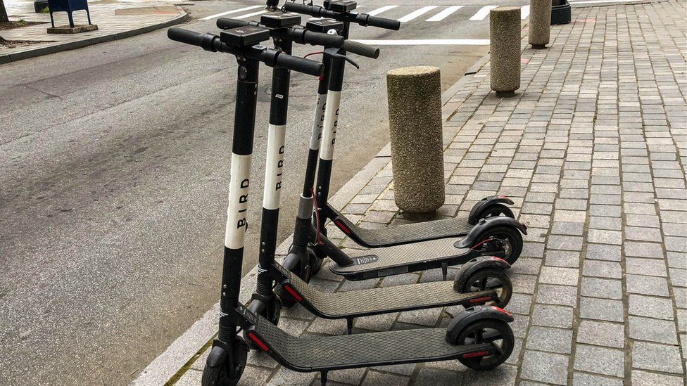 Four electric scooters are shown lined up on the side of the street.