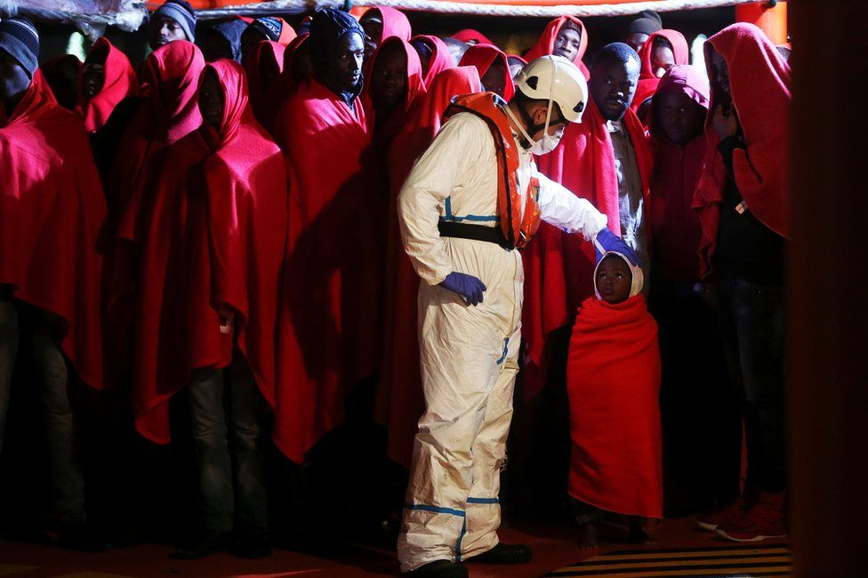 Migrants stand on a rescue boat