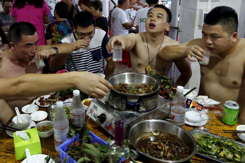 Men eating dog at the Yulin dog-meat festival