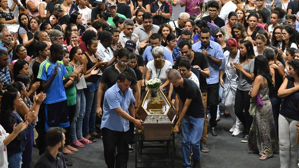 The coffin of one of the victims of the Raul Brasil public school shooting is wheeled by mourners
