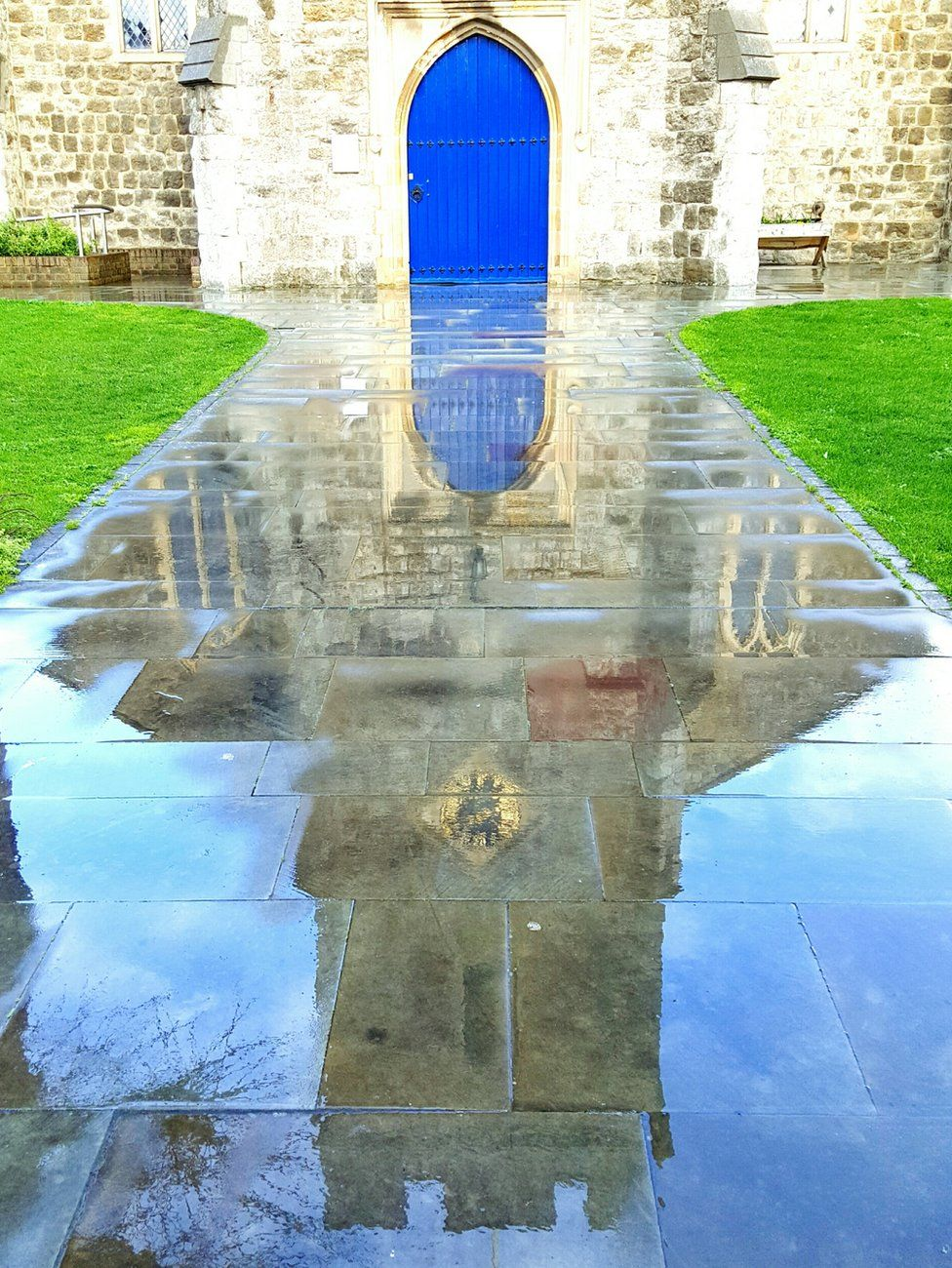Reflection of a church door on a wet path