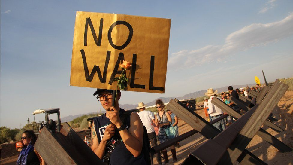 American activists hold signs at the border between the US and Mexico during a protest against the new construction plan of a steel wall between Santa Teresa, New Mexico, and Ejido San Jeronimo, in the municipality of Juarez, Chihuahua state, Mexico, on June 2, 2018 in Ciudad Juarez.