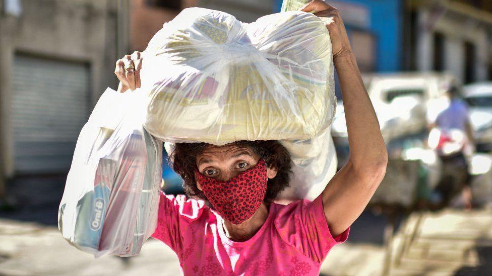A woman, a poor resident of the Serra Aglomerado Favela, receives food supplies in Belo Horizonte