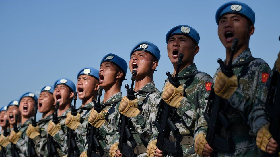 A row of Chinese soldiers shouting during marching drills