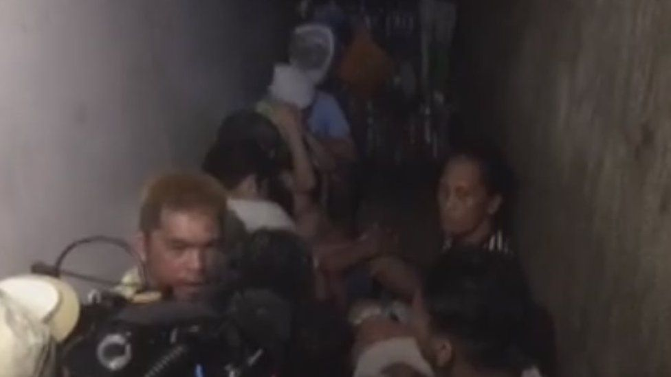 A screen grab from ABS-CBN news, showing people sat in a narrow and dark room