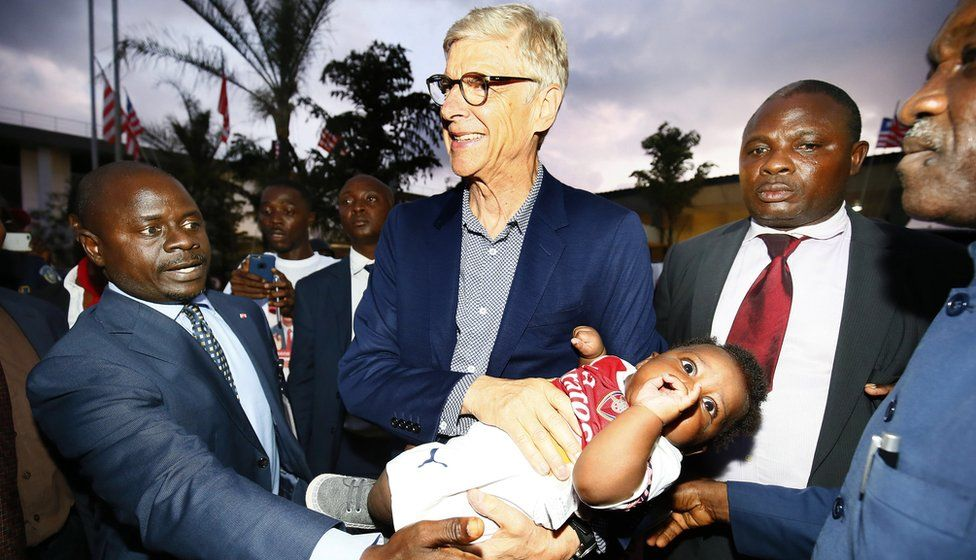 Former soccer coach Arsene Wenger (C) holds a baby dressed in Arsenal colors upon arrival at the Roberts International Airport in Harbel, Liberia, 22 August 2018.