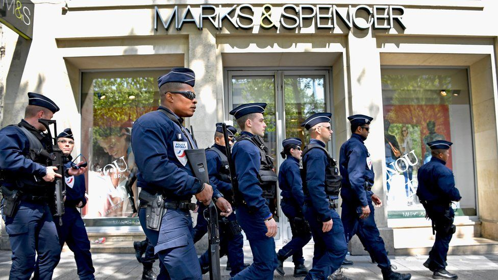French police walk past Marks & Spencer, 21 April, where their fallen colleague was shot on the Champs Elysees in Paris