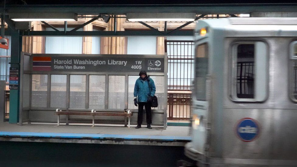 """A commuter waits for an """"L"""" train during rush hour in the Loop on March 20, 2020 in Chicago, Illinois."""