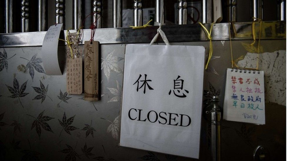 Messages of support (L and R) are seen hanging on the door of a closed bookshop selling books about China's politics in Hong Kong on January 4, 2016