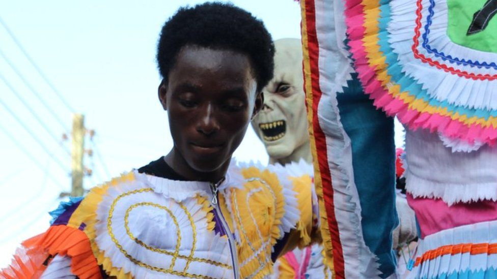 Man dressed in costume made with multi-coloured, chequered fabric. Lurking behind him, someone in an alien costume in Sekondi Ghana