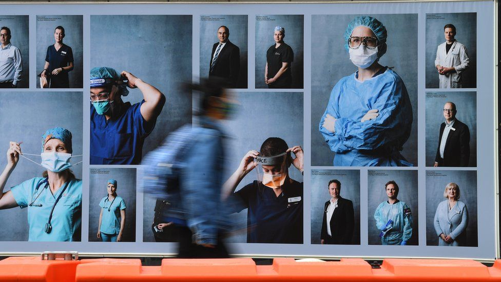 Person wearing a mask walks past a billboard in Melbourne featuring healthcare workers
