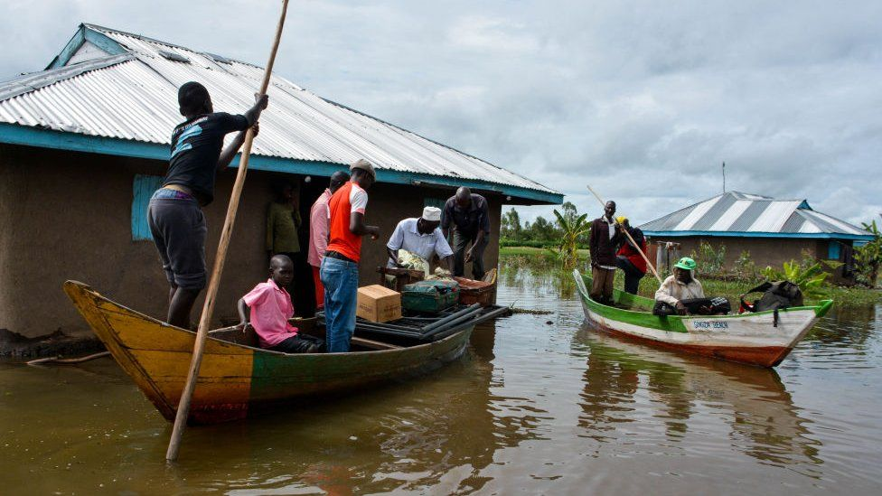 Rescue boats evacuate families after their houses were flooded in K'akola village in Nyando sub-county in Kisumu
