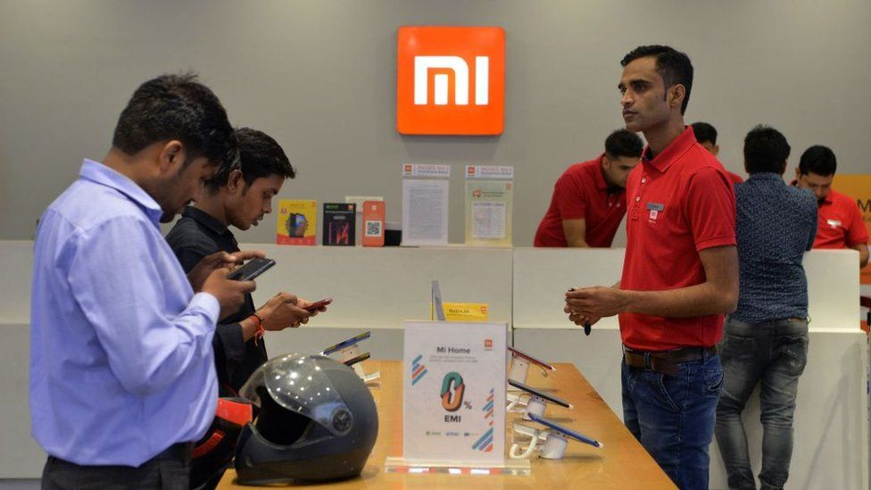 In this photograph taken on August 20, 2019, customers inspect smartphones made by Xiaomi at a Mi store in Gurgaon.
