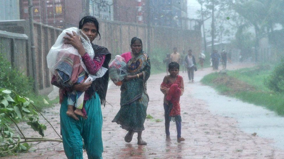 Bangladeshi people walk through waterlogged streets in Chittagong district