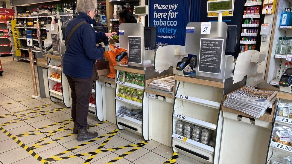 Taped-off areas for customers distance themselves from each other are seen at the checkout till area of a local Tesco store as the number of coronavirus disease cases (COVID-19) grow around the world, in London, Britain, March 21, 2020. REUTERS/Toby Melville