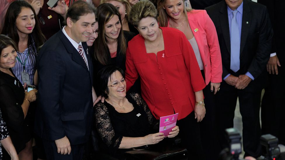 """Brazil's President Dilma Rousseff (in red) poses with women's rights activist Maria da Penha during the launch of the """"Woman: Living without Violence"""" program at the Planalto Palace in Brasilia March 13, 2013. The program seeks to prevent violence against women through educational campaigns. Maria da Penha, who fought for 20 years to see her assailant arrested, has a law named in her honor for victims of domestic violence against women."""