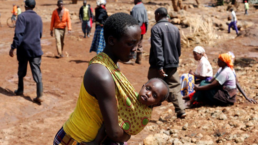 A woman carries her child as she walks near destroyed houses by flooding water after a dam burst, in Solio town near Nakuru, Kenya on 10 May 2018.
