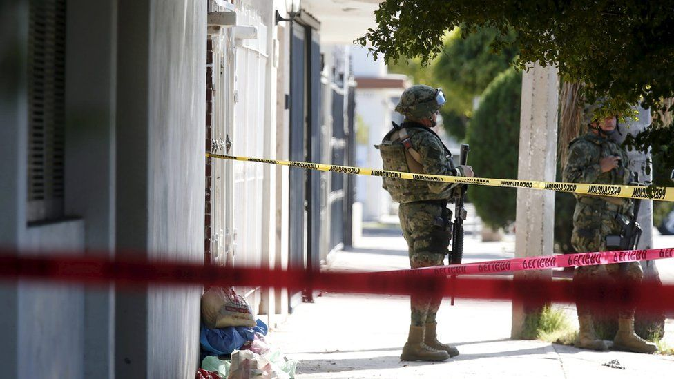 Soldier outside the house where five people were shot dead