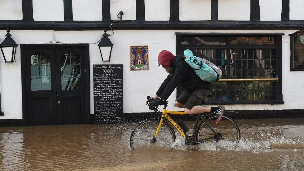 Man cycling through floodwater in Hereford