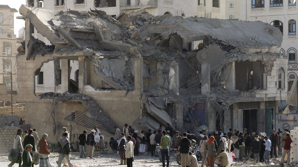 People gather outside the house of court judge Yahya Rubaid after a Saudi-led air strike destroyed it, killing him, his wife and five other family members, in Yemen's capital Sanaa