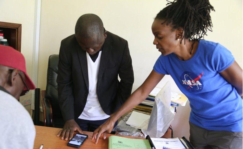 Dr Catherine Nakalembe talking to some men