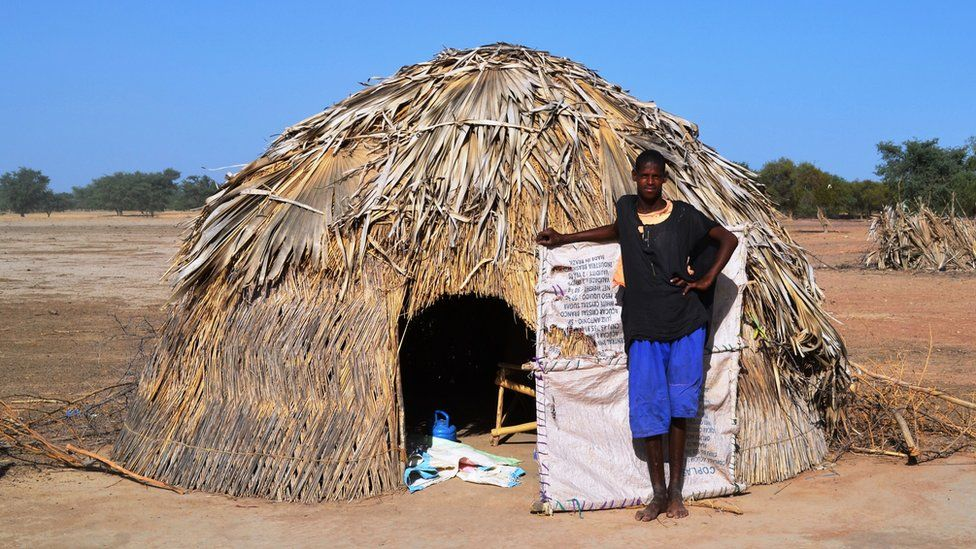 A young man standing by a a nomad hut