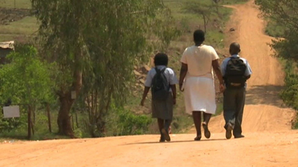 Woman and schoolchildren walking down the road