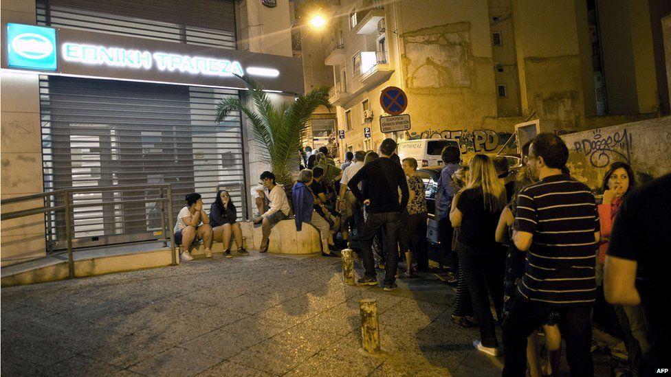 Greek people queue in front of an ATM in Athens