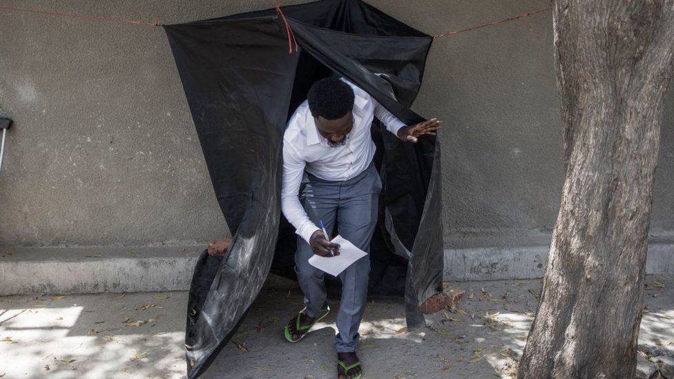 A man carries a marked ballot as he leaves a voting booth hanged on the side of the road at a polling station in N'djamena on April 11, 2021.