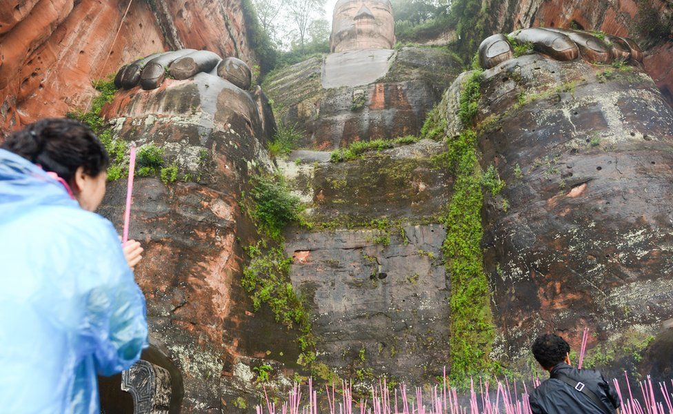 Tourists burn offerings at the feet of the Giant Buddha in 2016
