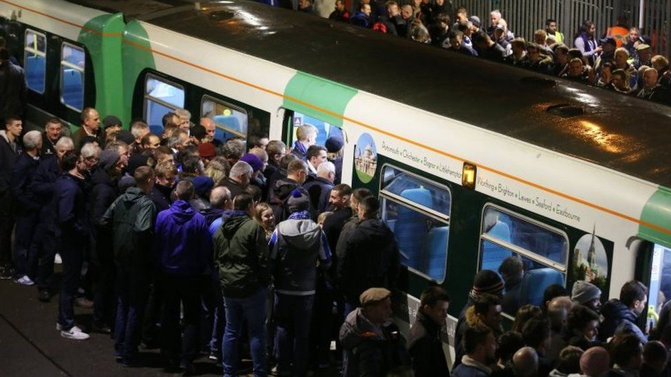 Football supporters boarding a Southern service