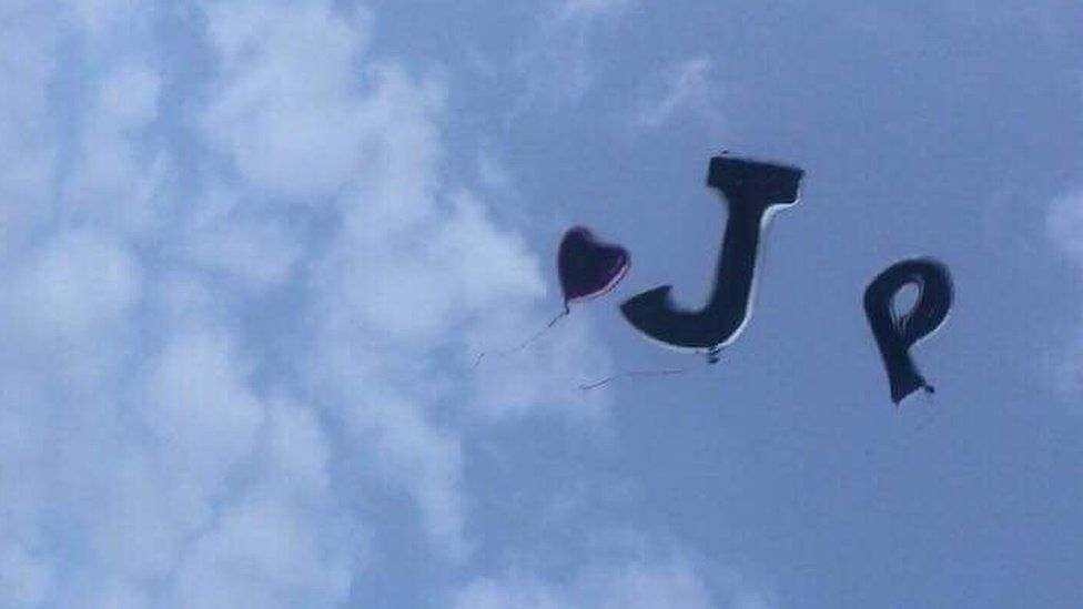 A heart-shaped balloon floating with others in the initials J P