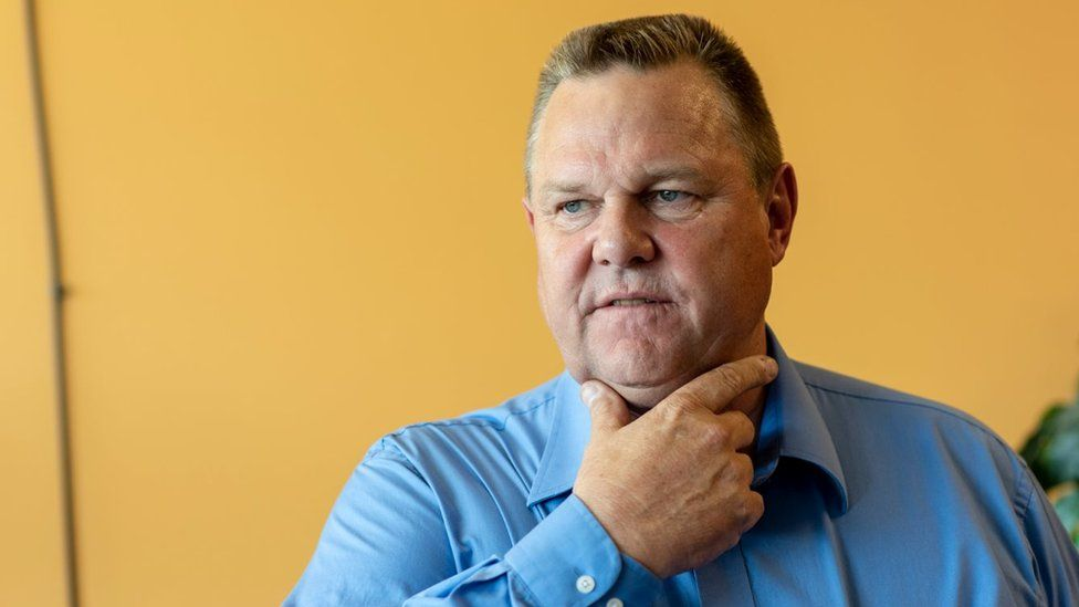 Jon Tester holds hand to face, wearing a blue shirt