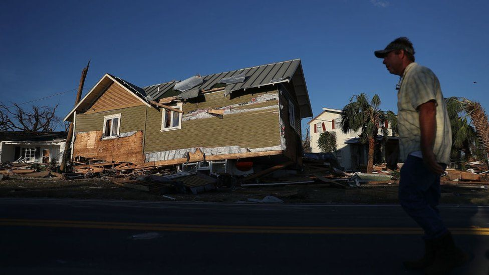 A man in Mexico Beach, Florida walks past a home that was knocked from its foundation