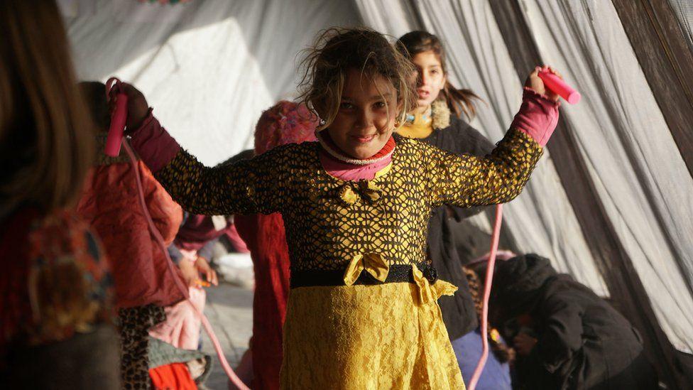 A girl skipping in a refugee camp in Iraq