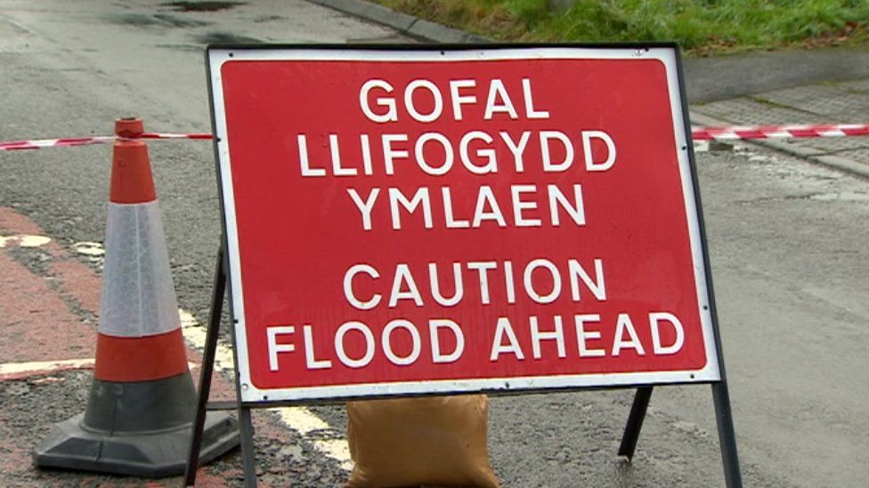 A sign reads 'caution flood ahead'