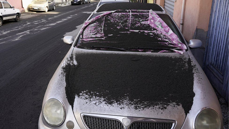 A car is covered in volcanic ashes from Mount Etna in Santa Venerina, Italy, 28 February 2021