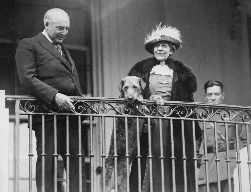 President Warren G Harding and First Lady Florence Harding stand on a balcony with their dog