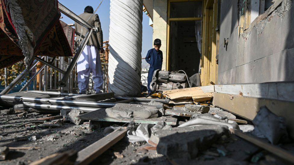 People inspect a damaged house after several rockets landed at Khair Khana