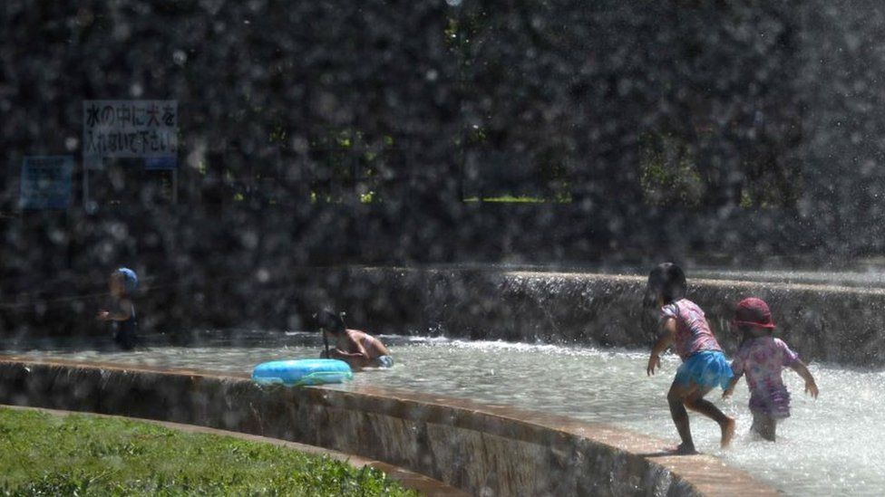 Children play in a water fountain in a Tokyo park, as a heatwave grips Japan, 10 July 2018