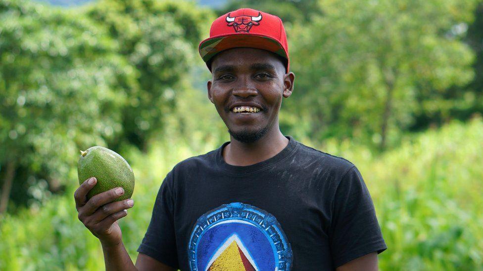 Avocado oil press inventor Jesse Oljange in a field with an avocado
