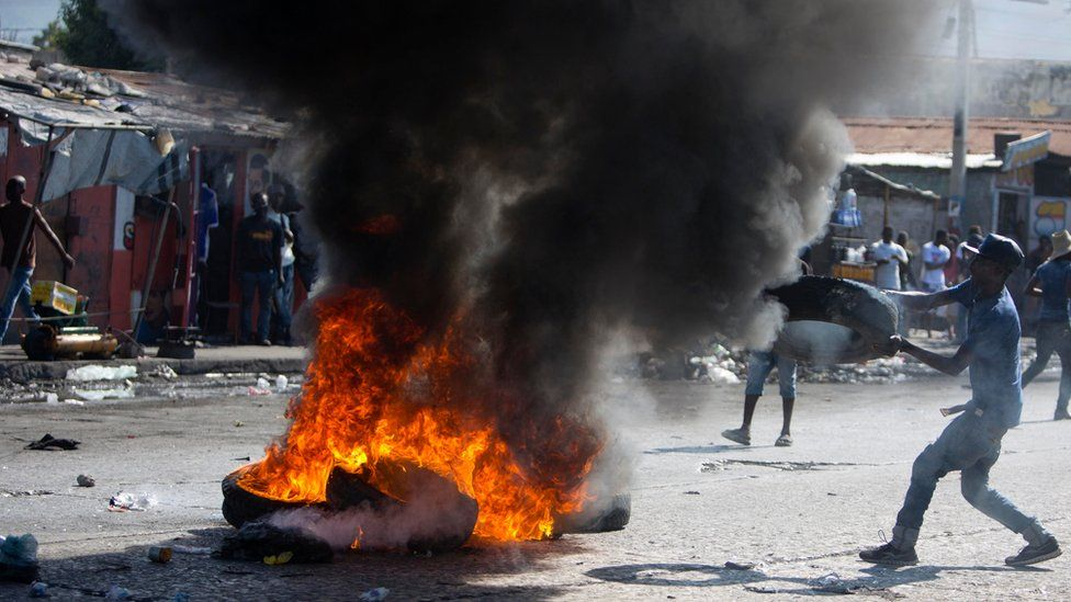 A supporter of presidential candidate Maryse Narcisse burns tires to protest the final election results in Port-au-Prince, Haiti